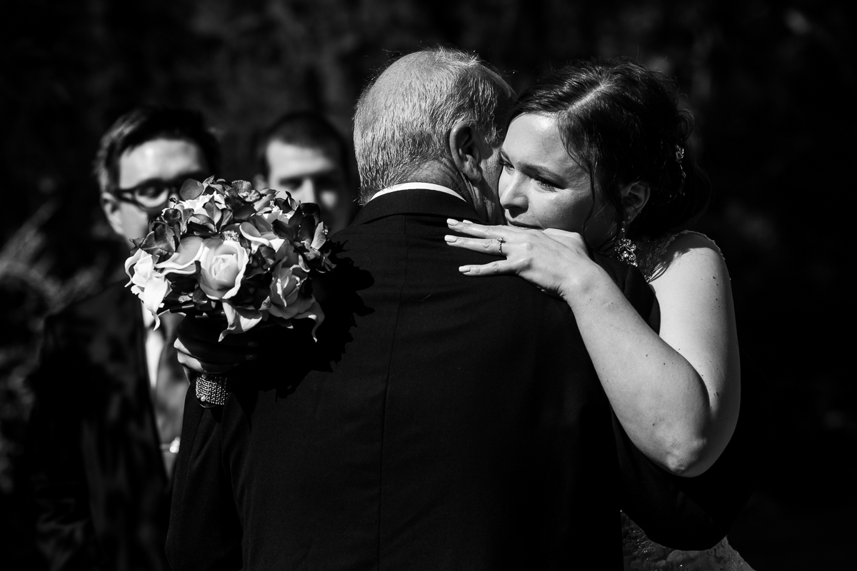 bride hugging dad one last time before greeting groom at altar in black and white holding bouquet