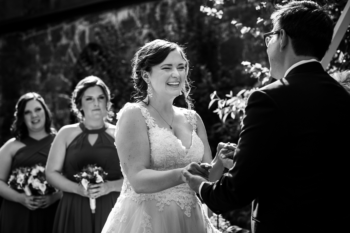 black and white photo of bride and groom holding hands while saying vows during ceremony while bridesmaids smile in background