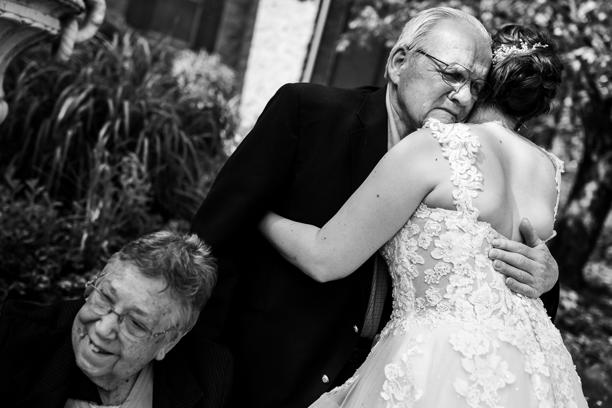 black and white photograph of grandfather hugging granddaughter bride after ceremony while grandmother smiles