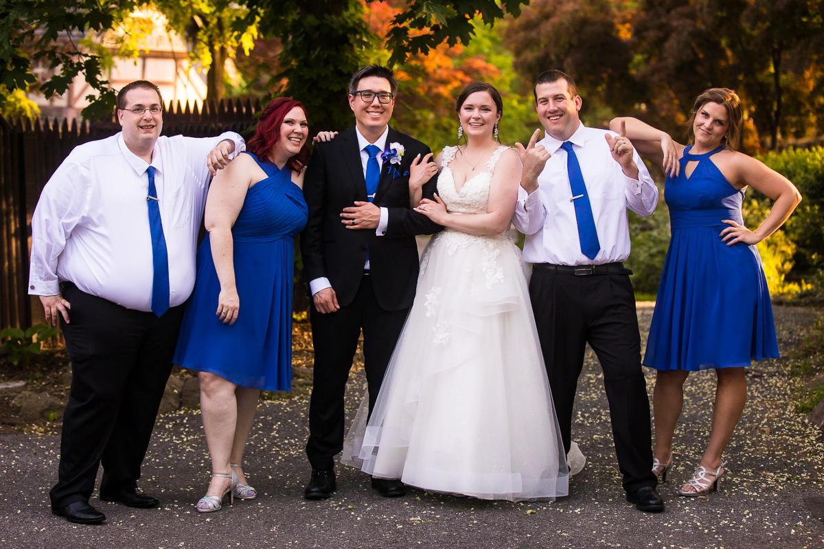 fun creative wedding party photo blue bridesmaid dresses blue groomsmen ties outdoors