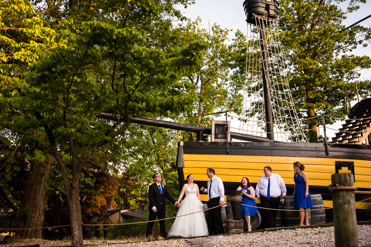 best renaissance fair wedding photographer Manheim pa wedding party in front of pirate ship laughing with bride and groom