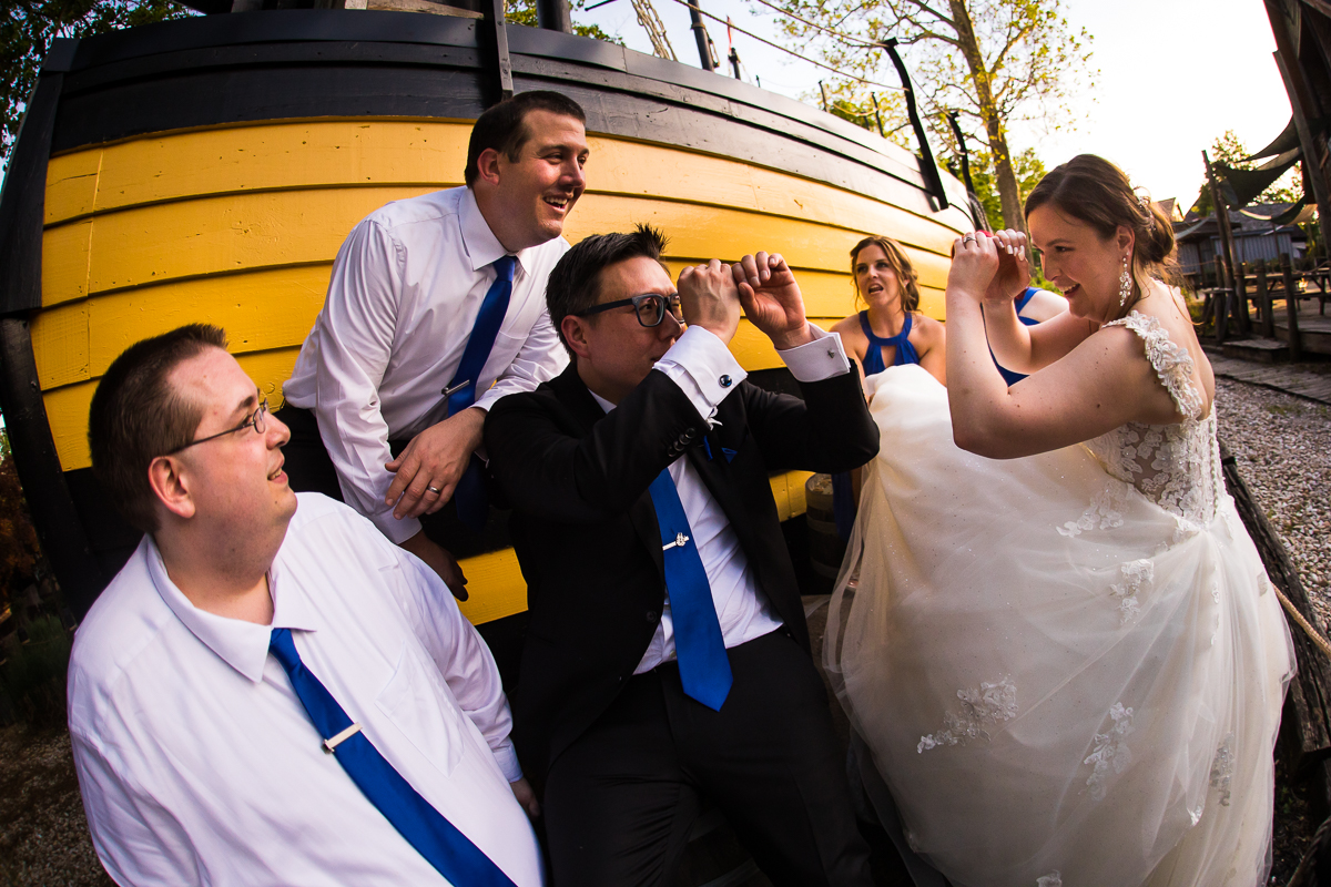 non-traditional wedding party group photos with bride and groom pretending to look through telescope in front of pirate ship