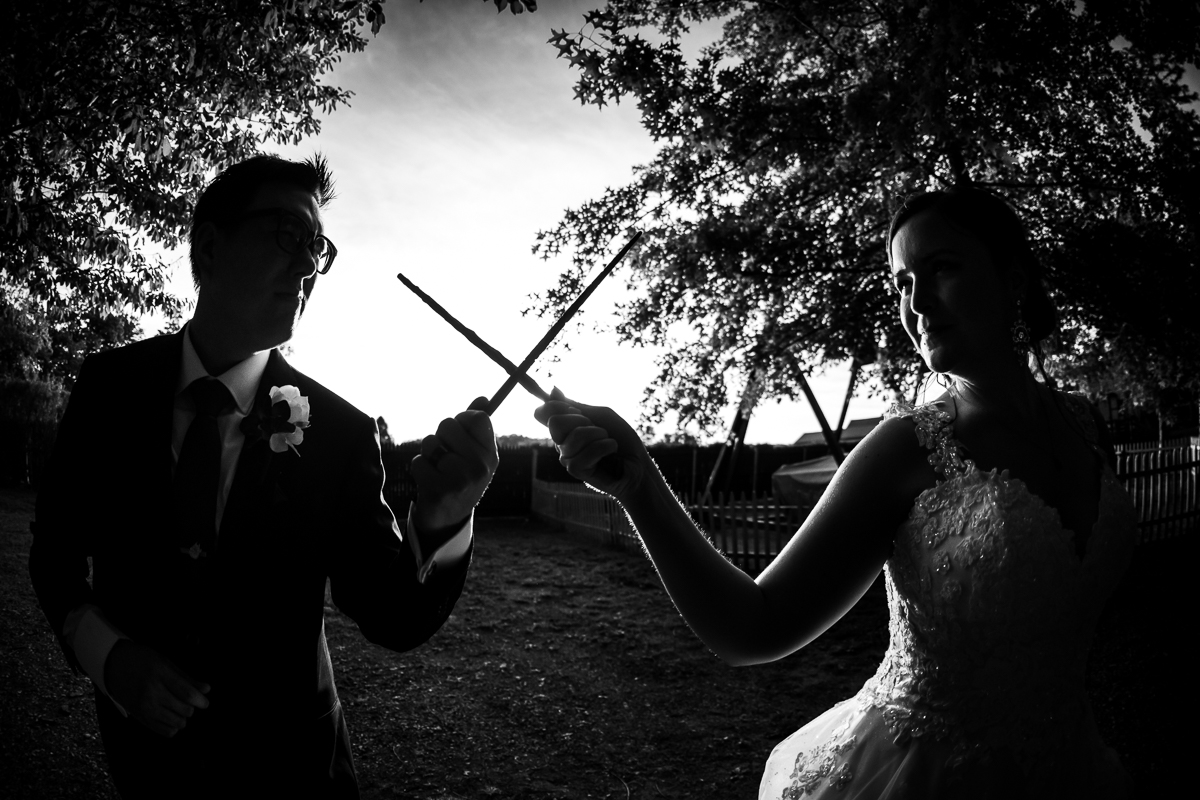 harry potter themed wedding bride and groom pointing wands at each other black and white photo on renaissance faire grounds Manheim pa