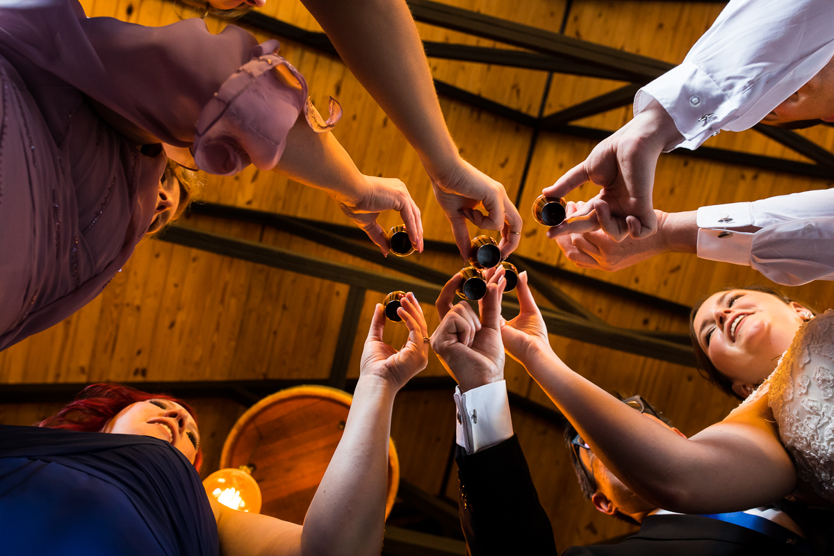 wedding guests taking shots together creative viewpoint angle from below