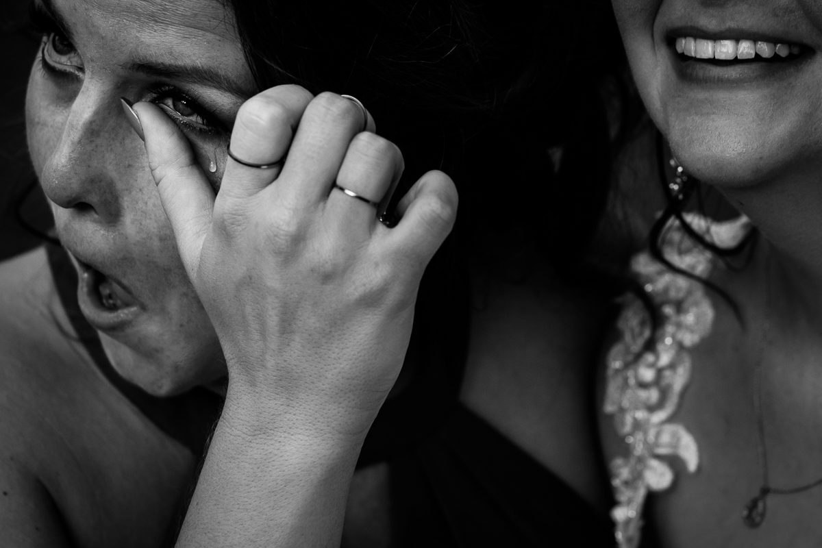 emotional black and white photo sister wiping tear from eye at bride's wedding