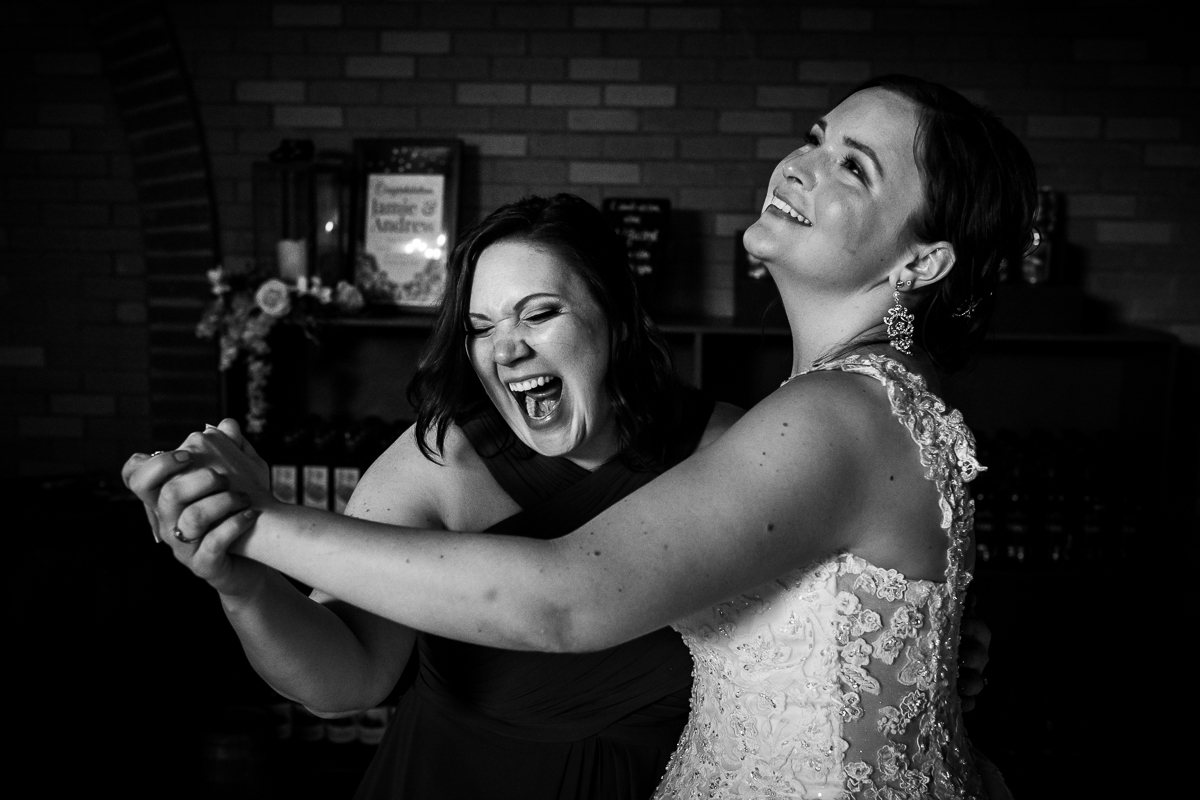black and white photo of bride dancing with bridesmaid during Hamilton song at wedding reception
