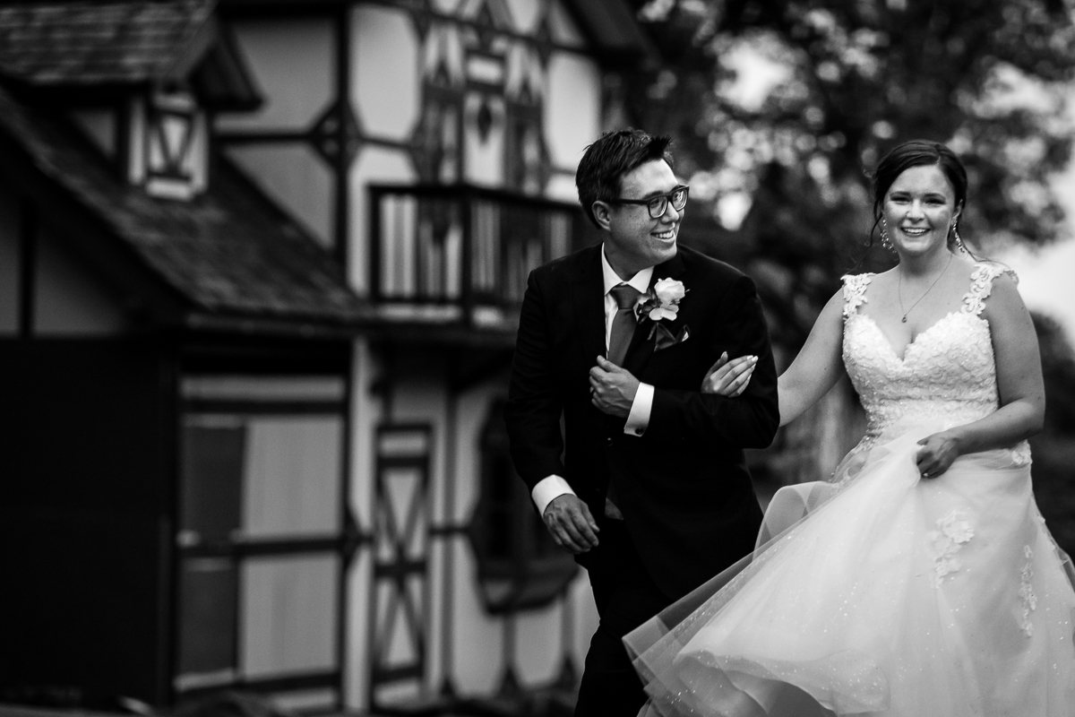 black and white wedding portrait of bride and groom smiling walking at renaissance fairgrounds