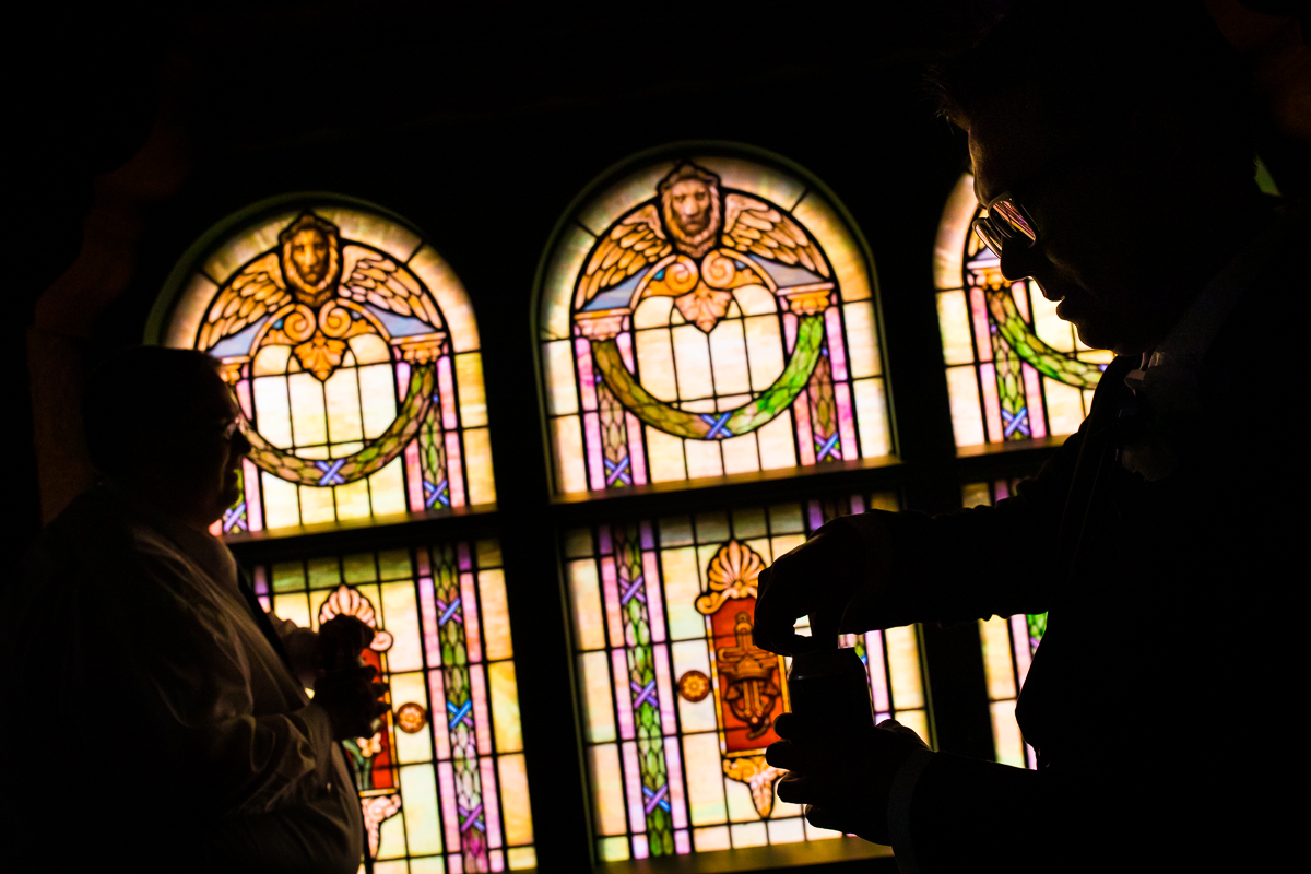 creative silhouette photo of groom and groomsmen opening beer in front of stained glass window