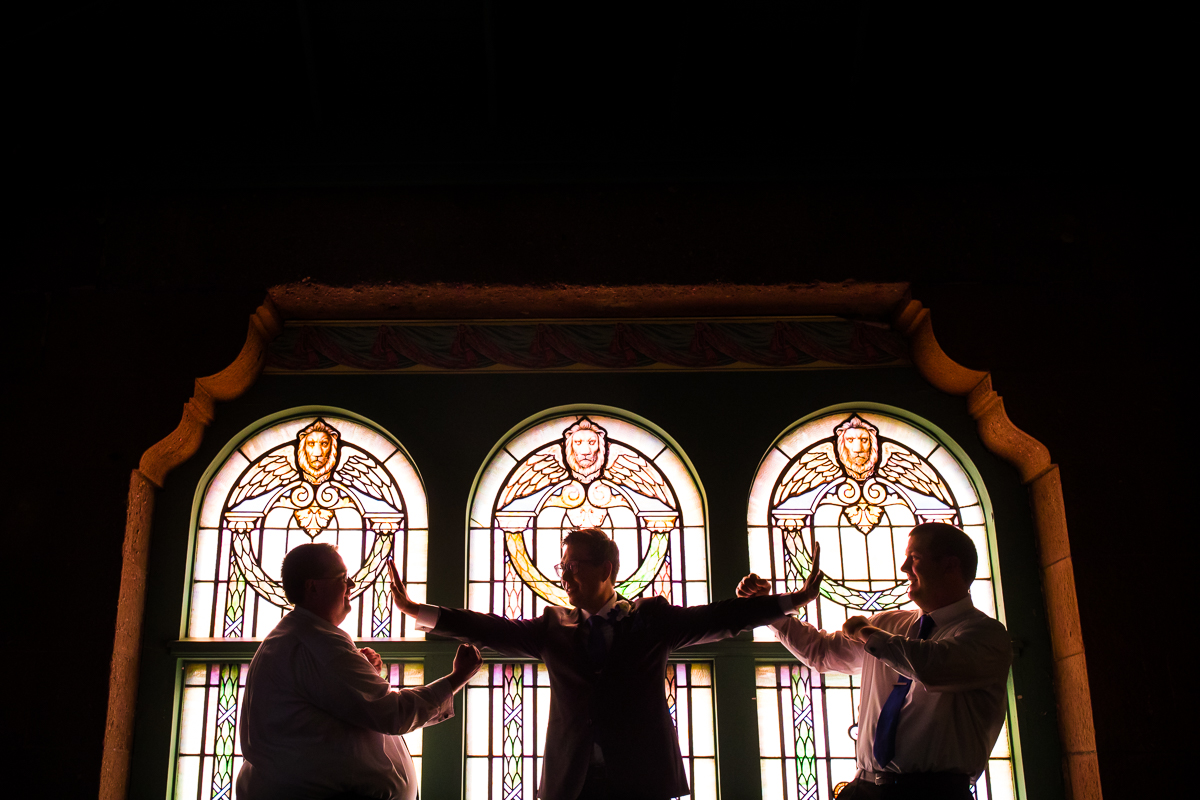 groom and groomsmen Star Wars force photo in front of stained glass windows during getting ready