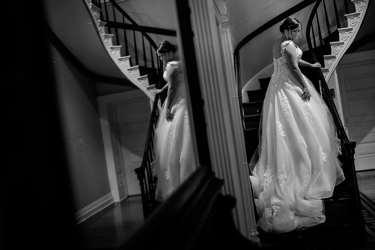 black and white photo of bride walking up staircase smiling and looking back with dress train behind reflection in mirror