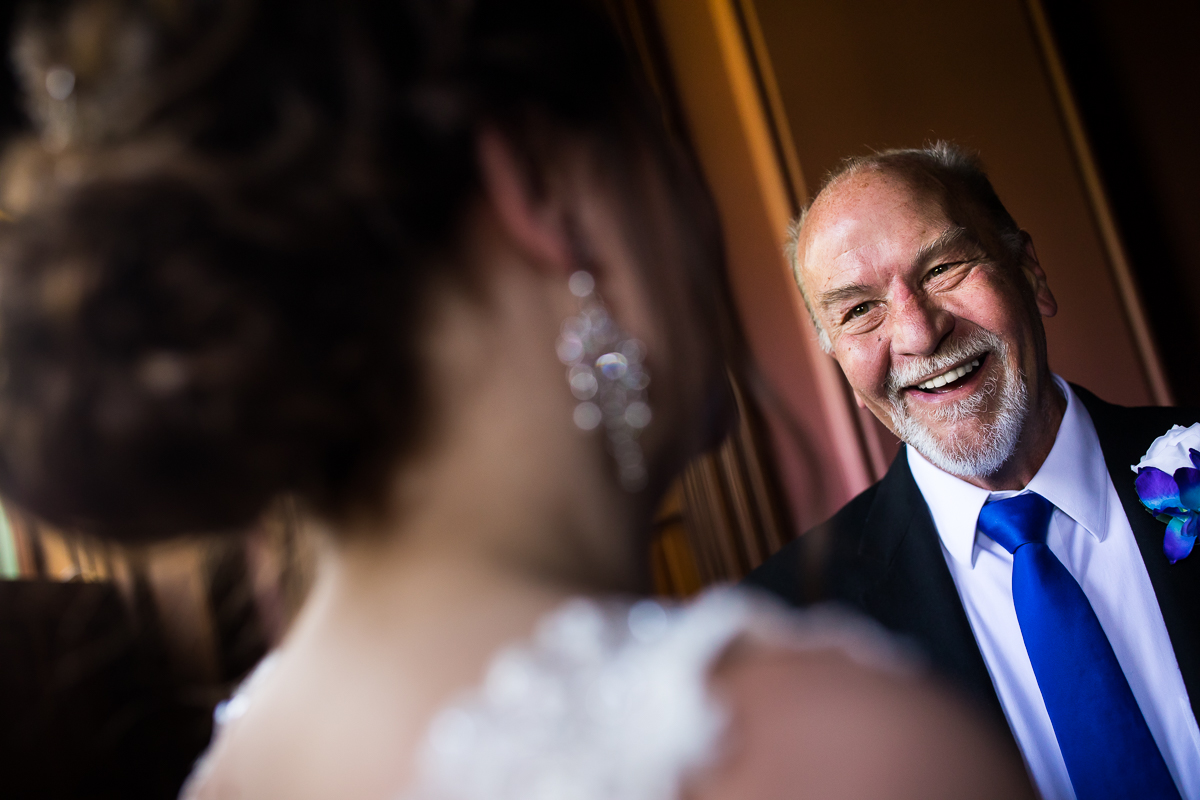 bride and father first look dad smiling while looking at daughter on wedding day in wedding dress