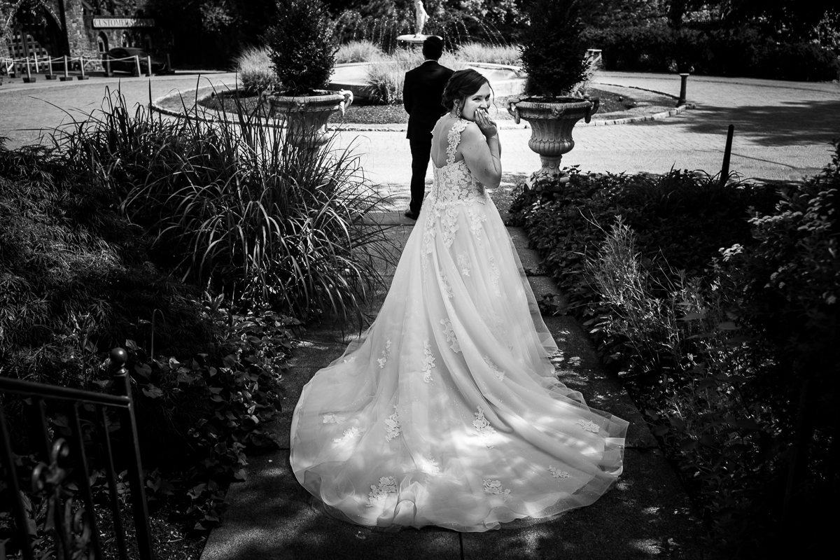 black and white bride and groom first look bride looking at camera while walking up to groom outside at mount hope estate