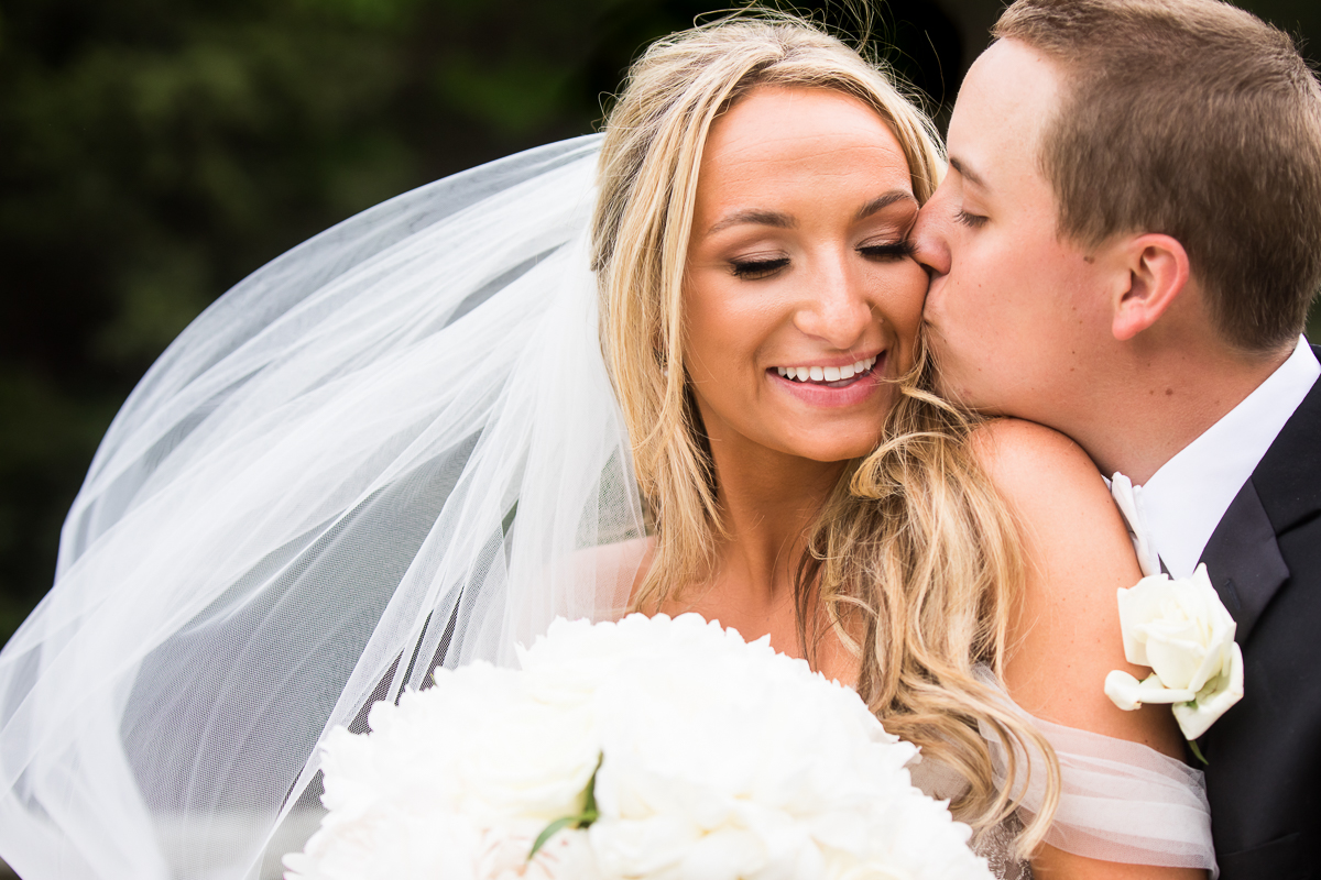 omni bedford springs wedding groom kissing bride on cheek on wedding day best omni springs wedding photographer creative award winning creative authentic candid omni wedding photographer