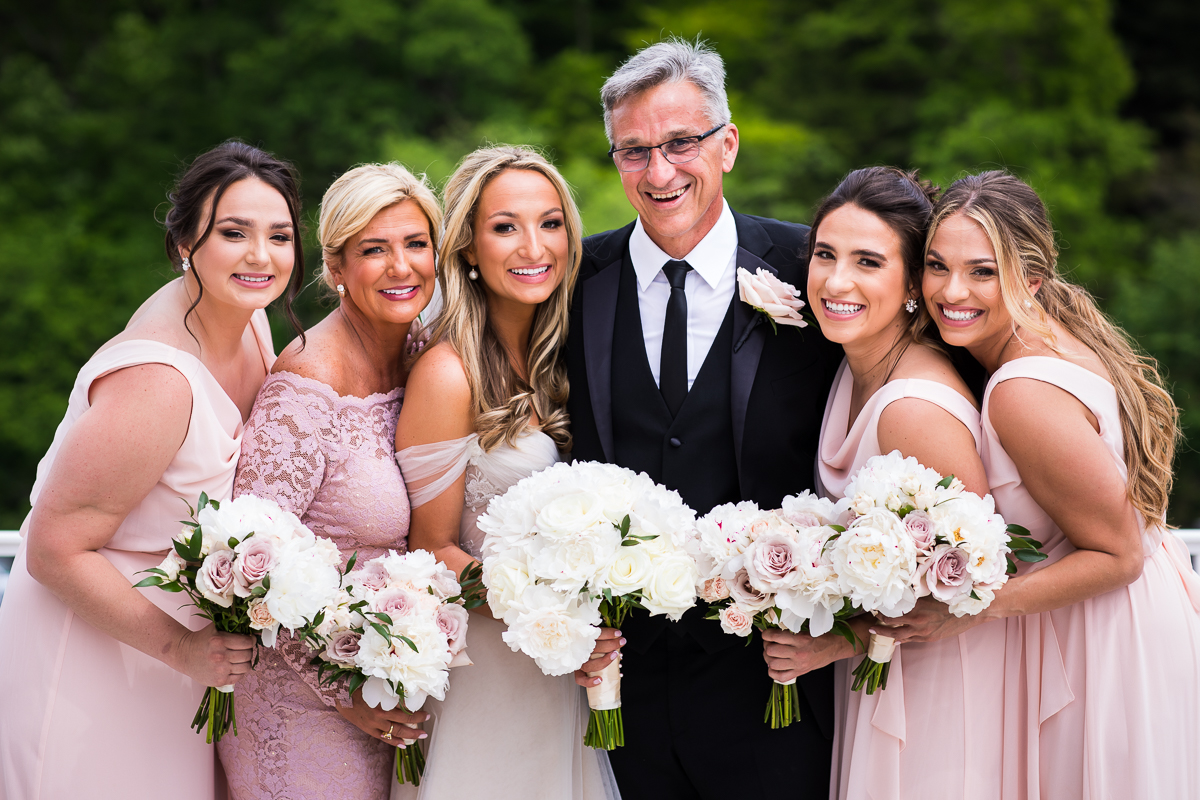 father of the bride with bride mom and daughters traditional family portrait outside