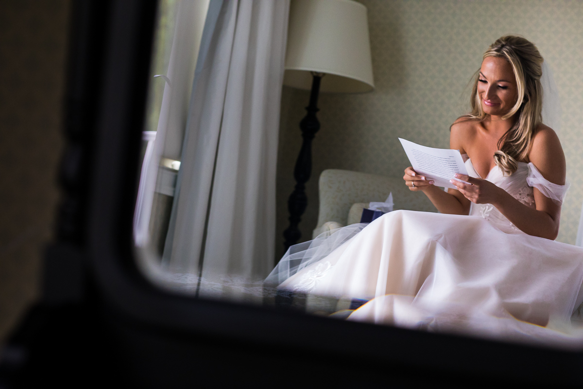 bride reading letter from groom morning of wedding smiling emotional creative perspective wedding photographer