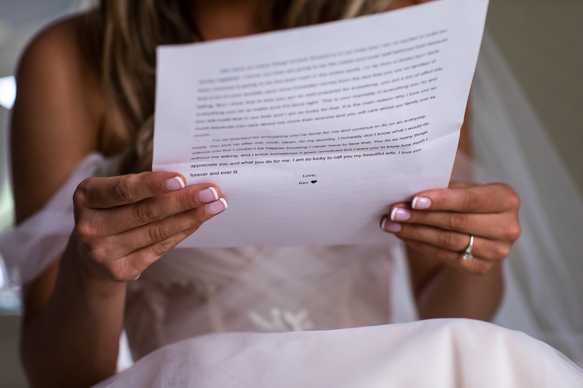 close up photo of groom's letter to bride on wedding day bride holding letter with French manicure