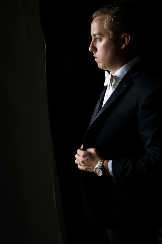 mood lighting groom looking out window holding suit jacket open