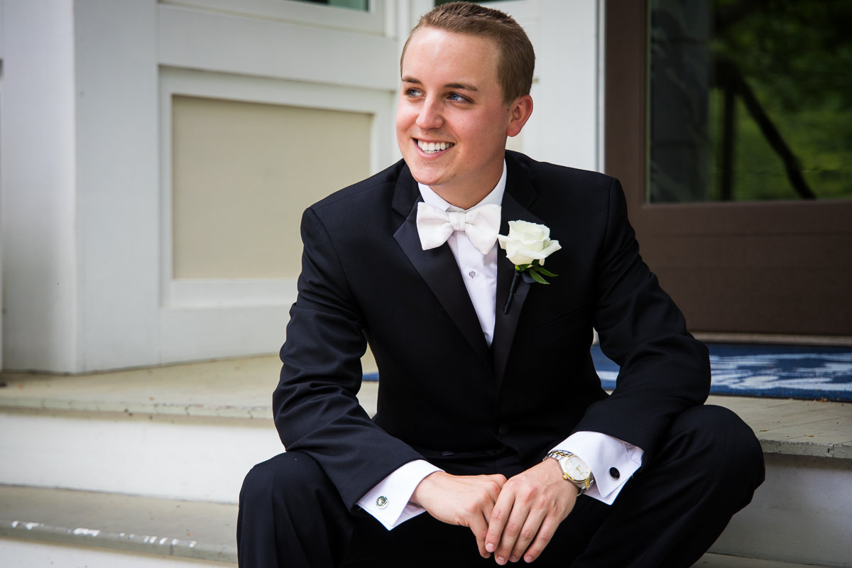 portrait of groom smiling looking off into the distance sitting on steps during portrait wearing white bow tie