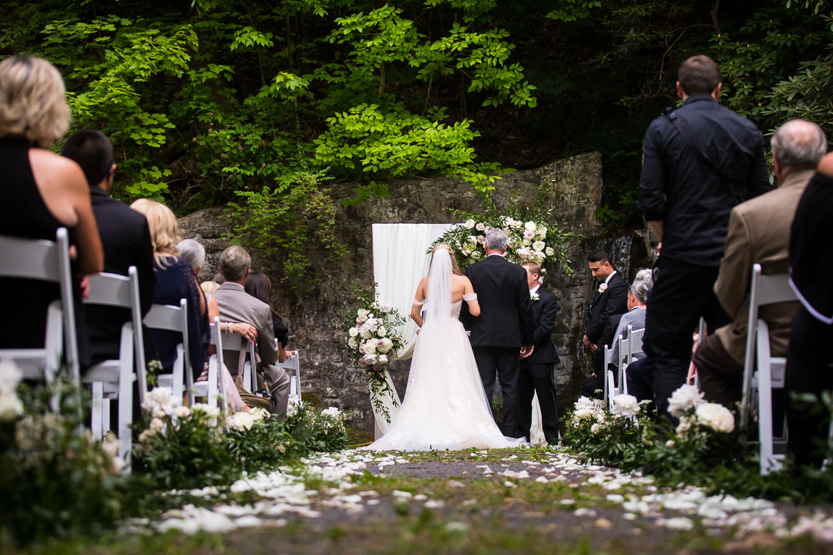 father of the bride giving away daughter to groom before wedding ceremony flower lined aisle with white chairs grotto at Omni Bedford Springs