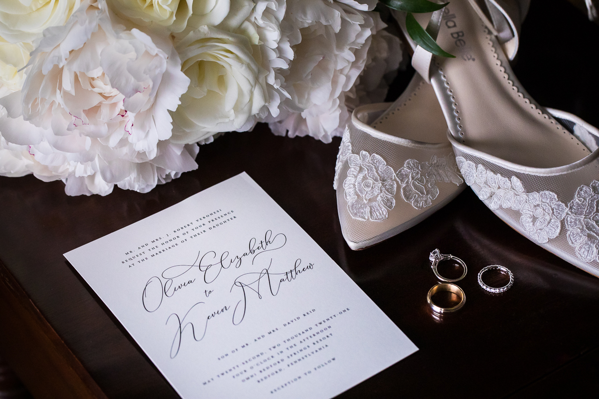 bride detail photo with wedding invitation Bella belle wedding shoes wedding rings and white flowers