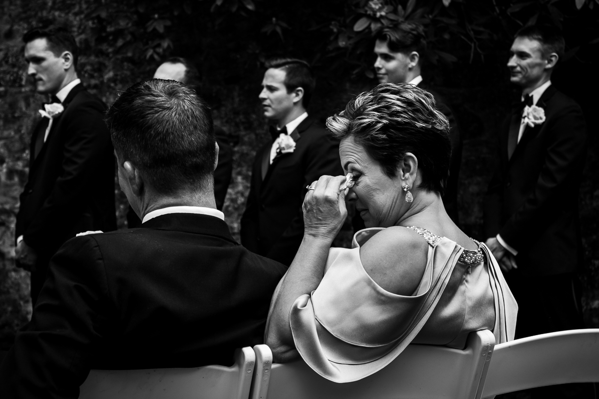 black and white photo of groom's mom crying during wedding ceremony emotional best photographer