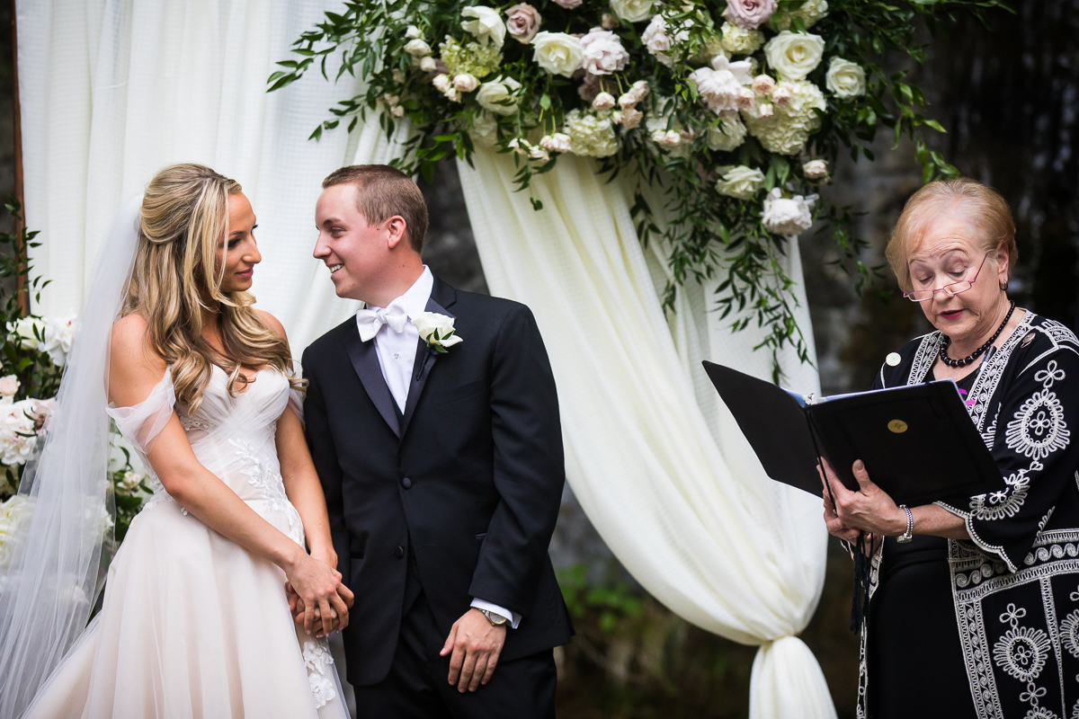bride and groom holding hands smiling at each other while officiant starts wedding ceremony white curtains and flowers at altar