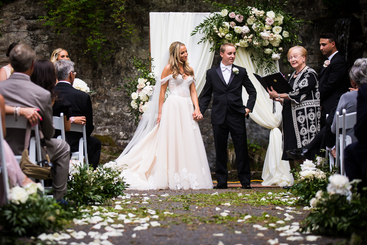 bride and groom holding hands during ceremony smiling at officiant during vows outside grotto award winning wedding photographer