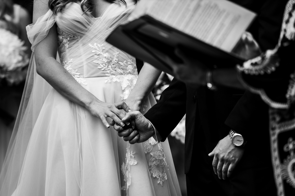 black and white photo of bride and groom holding hands during wedding ceremony while officiant reads