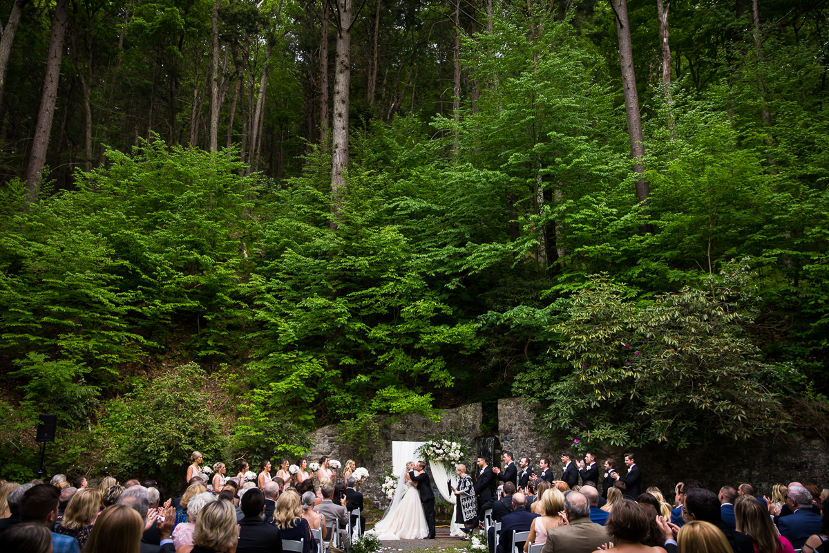 wide angle perspective bride and groom first kiss in grotto at Omni Bedford Springs with trees and greenery in background as guests smile watching