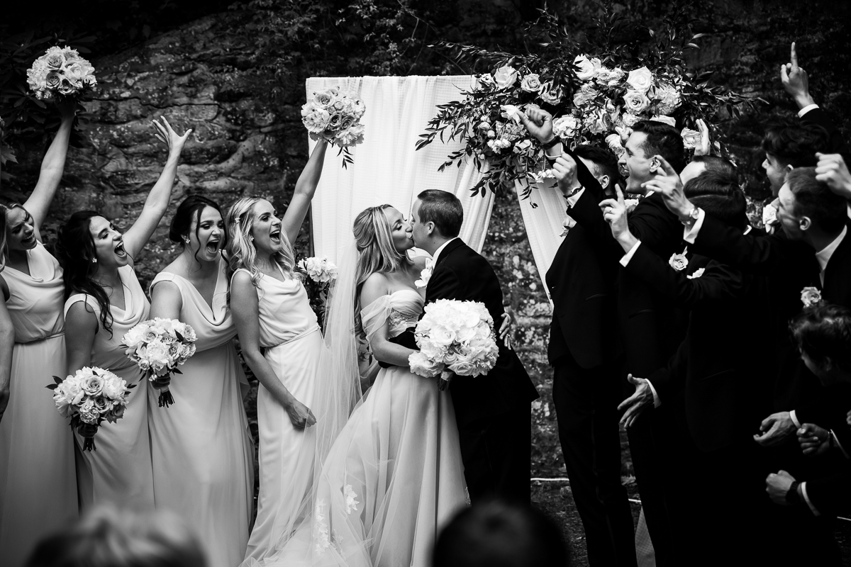 black and white photo of bridal party cheering while bride and groom have first kiss fun emotional