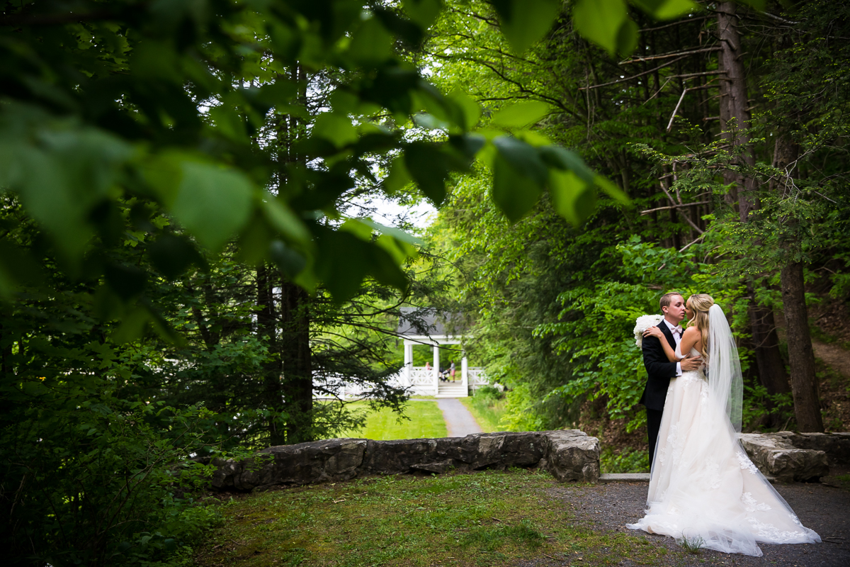 bride and groom holding each other while sharing a moment alone after wedding ceremony outside with greenery surrounding them