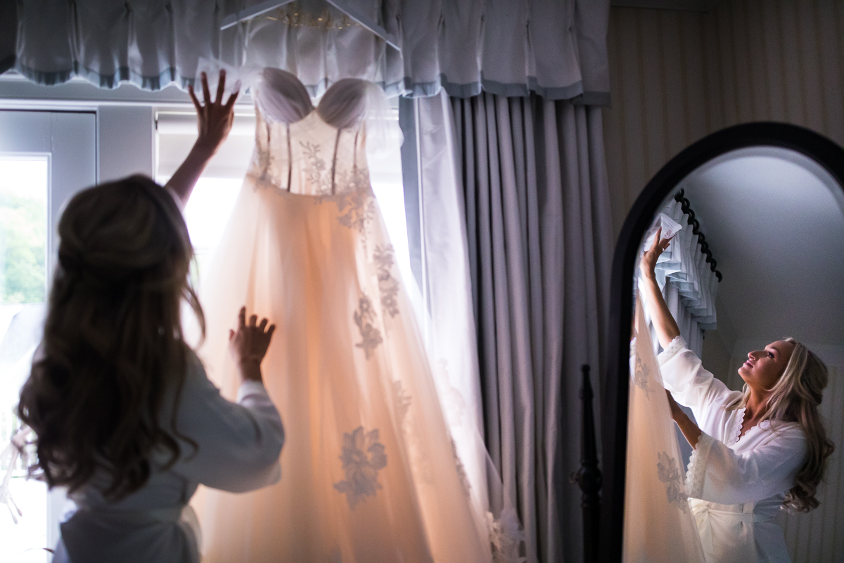 omni bedford springs wedding bride wearing robe looking at wedding dress hanging in front of a window reflected into mirror unique creative perspective