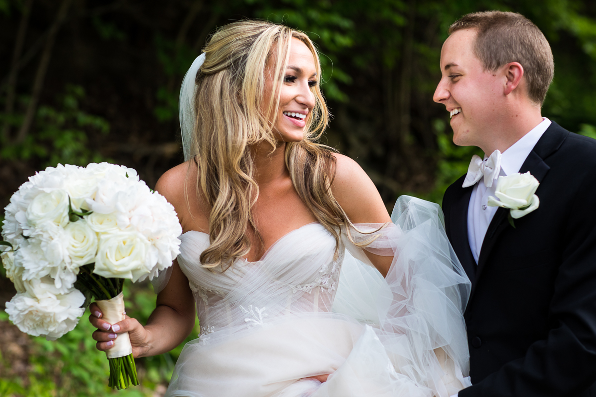 omni bedford springs wedding bride and groom walking smiling at each other holding white bridal bouquet