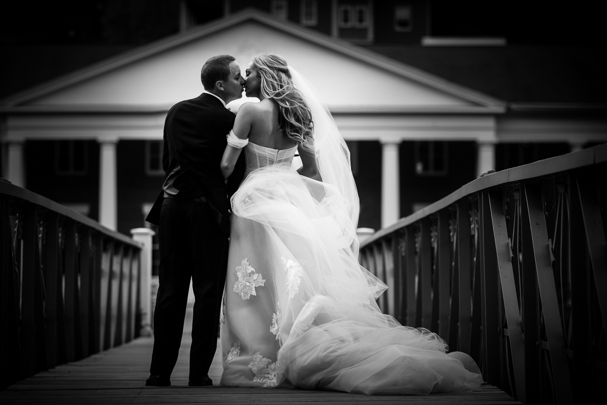 black and white photo of bride and groom sharing a kiss walking along bride at Omni Bedford Springs