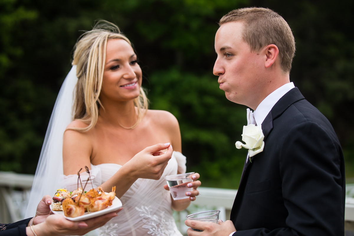 bride feeding groom hors dévoreurs during cocktail hour creative authentic candid omni wedding photographer
