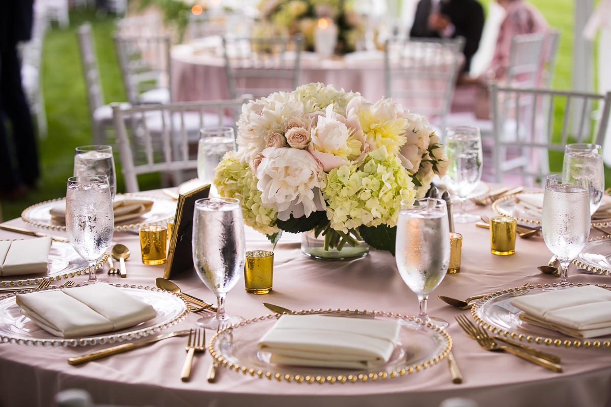 table place settings gold ringed chargers white bouquet in vase for centerpiece pink tablecloths