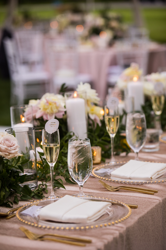 champagne glass seating chart with pink tablecloths and flowers and candles as centerpieces