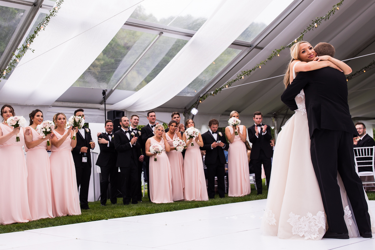 bridal party looks on during bride and groom emotional first dance outside in tent at omni Bedford springs wedding