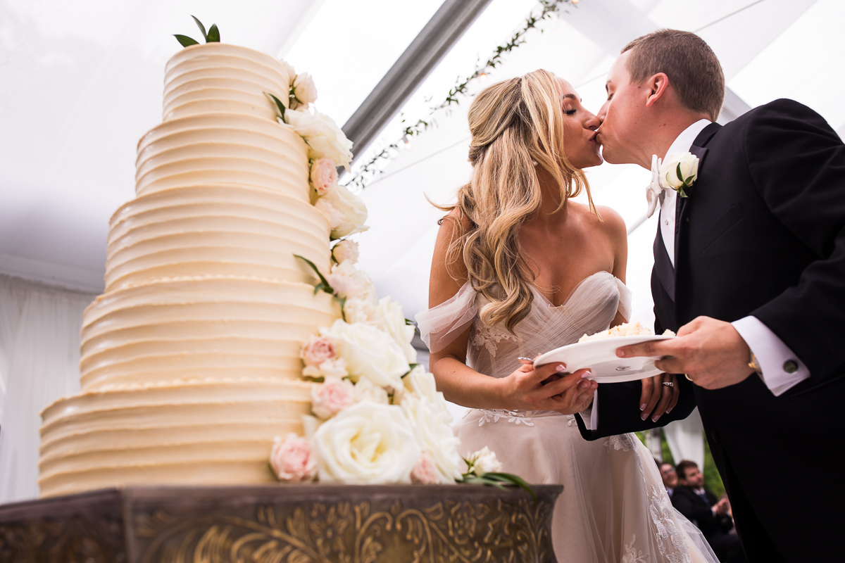 omni bedford springs wedding bride and groom kiss after cake cutting while holding cake with white icing and flowers cascading down it