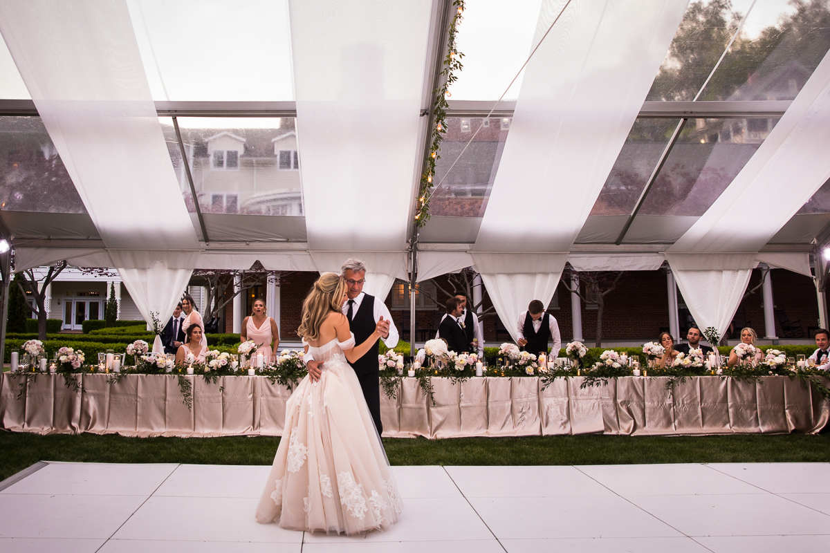 omni bedford springs wedding bride and father share dance in front of head table outside in tent with drapery from ceilings