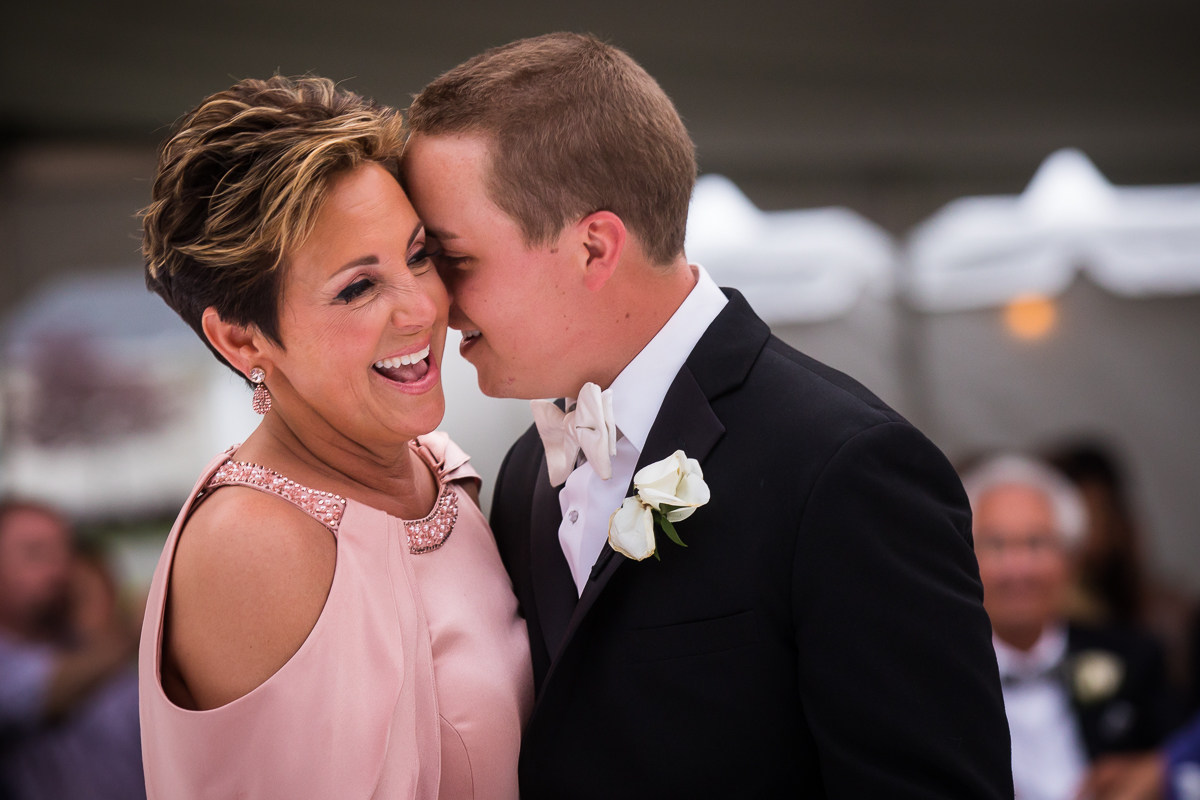 groom and mother share dance during wedding reception mom smiling