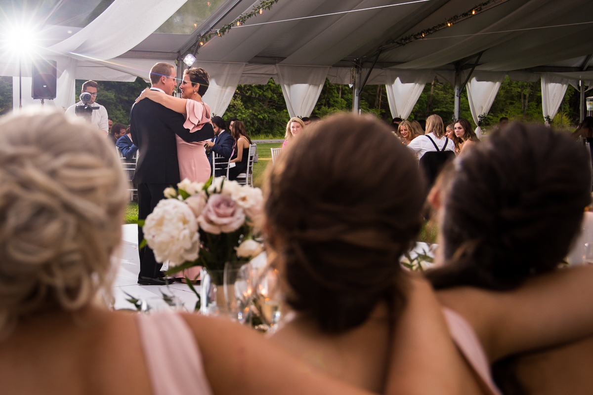 groom and mother share dance while bridal party members put arms around each other in foreground fun pennsylvania wedding photographer Omni Bedford Springs
