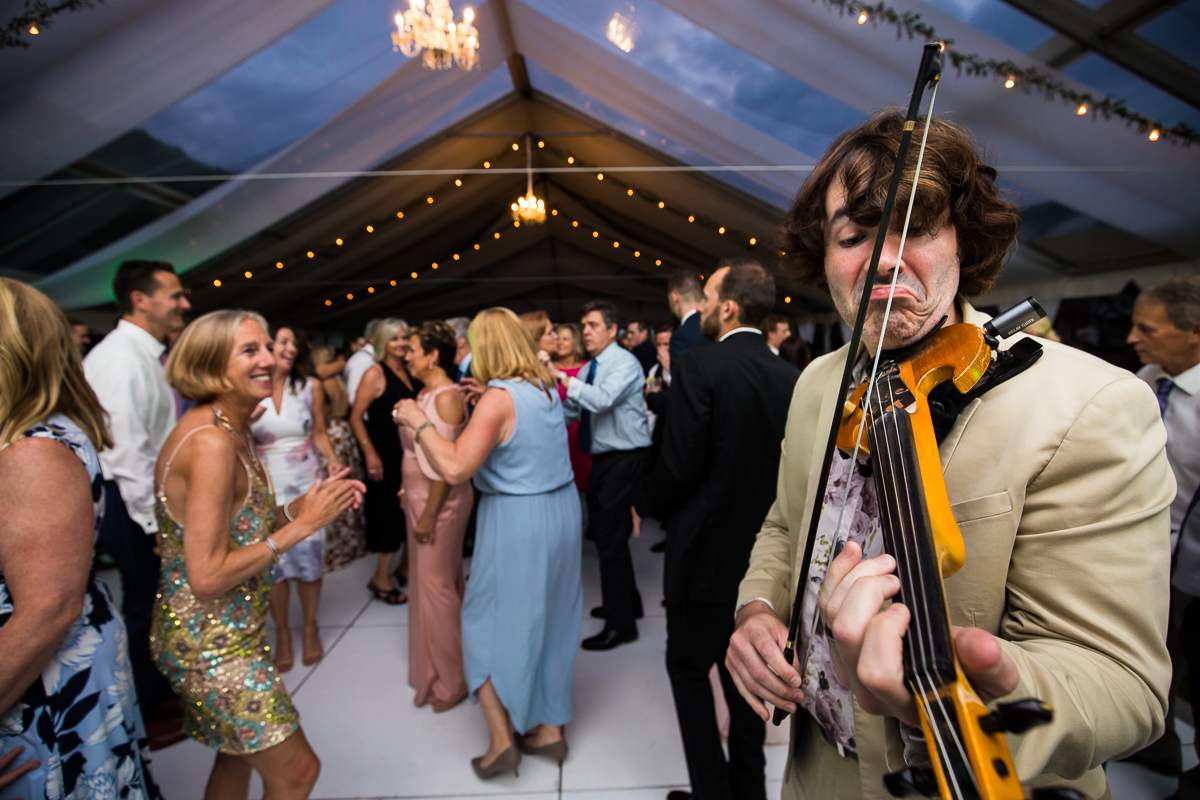 musician plays electric violin during wedding reception while guests dance in background with lights on tent