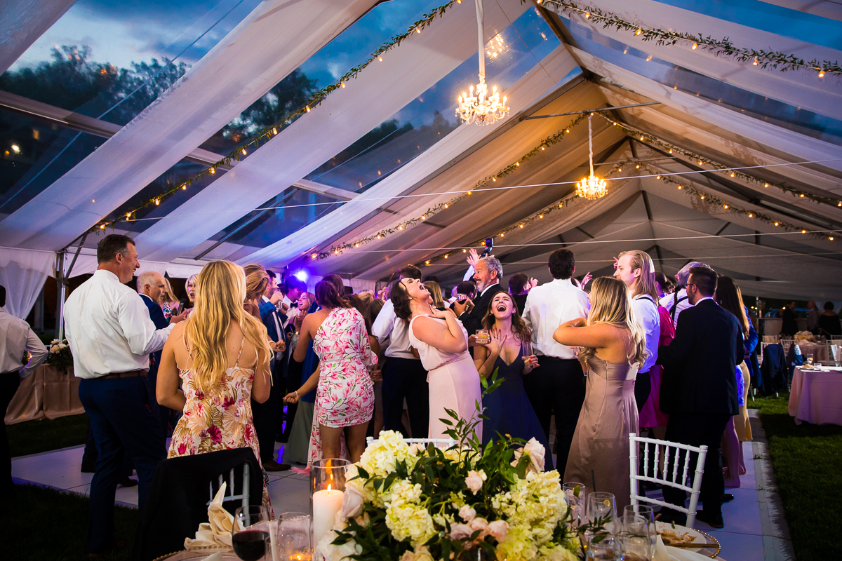 guests dance and sing during wedding reception under tent with drapery and string lights at omni bedford