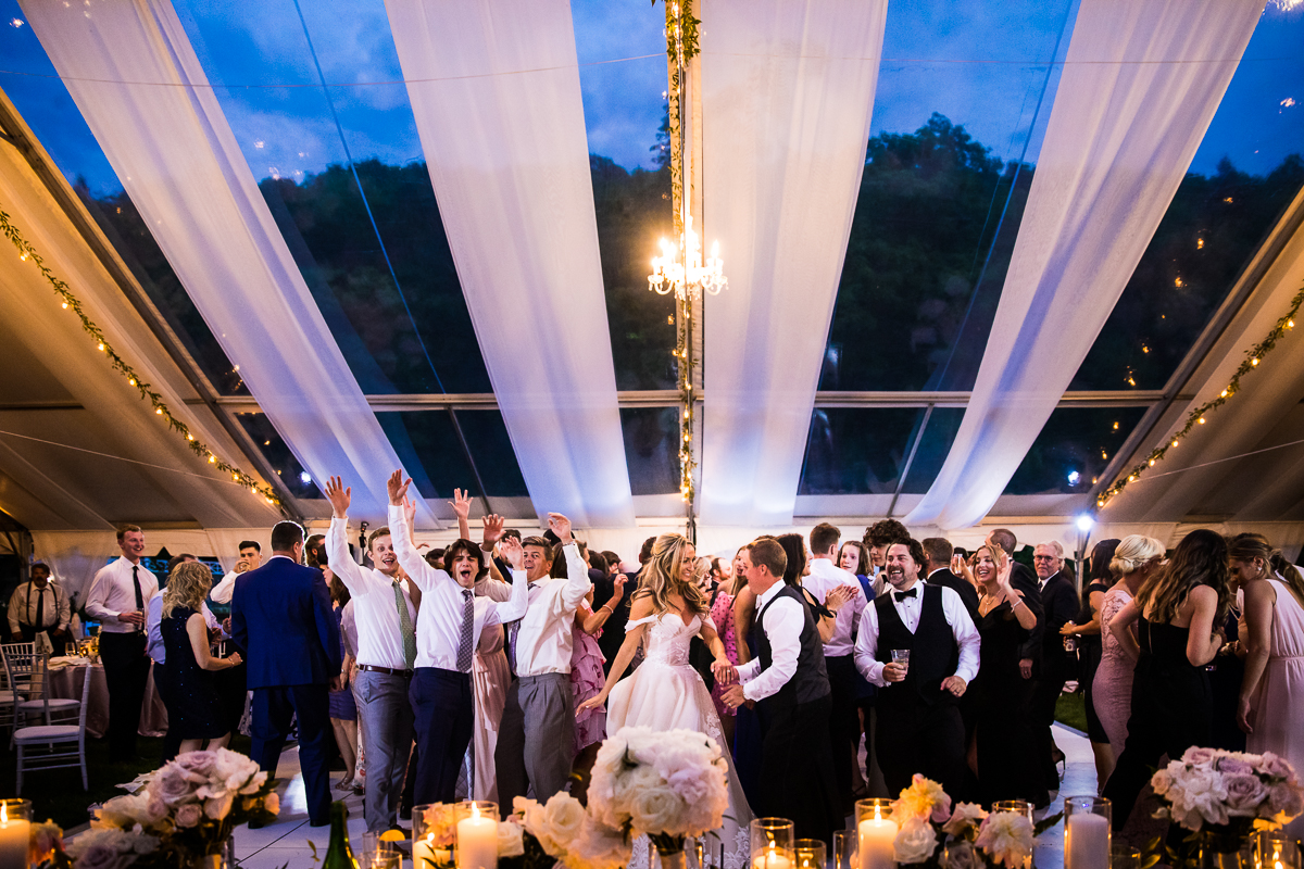 omni bedford springs wedding bride and groom and guests dance together during wedding reception under tent during twilight with gorgeous drapery and twinkle lights at Omni Bedford Springs best pa wedding photographer unique creative nontraditional fun