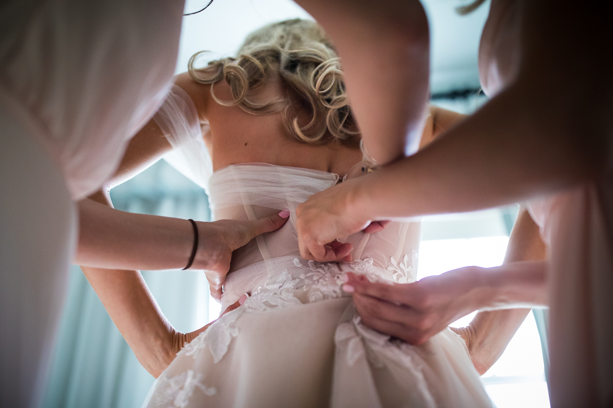 bridesmaid helping button up wedding dress while getting ready unique angle best pa wedding photographer