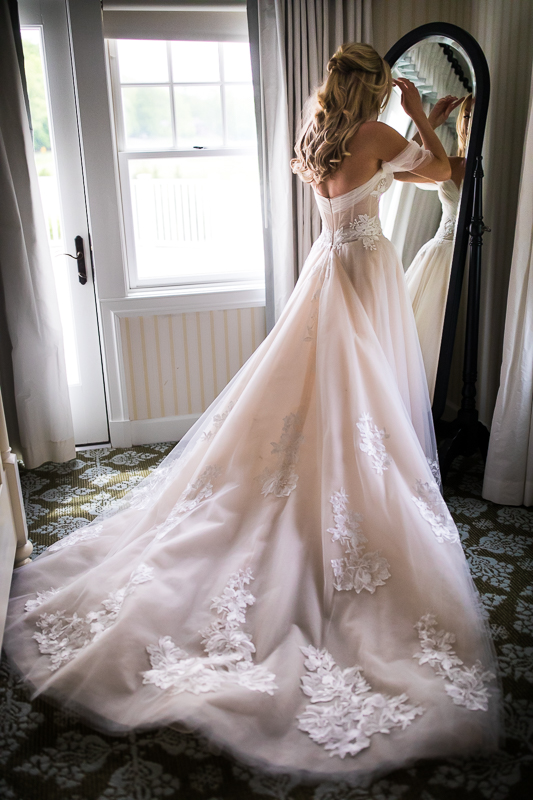 bride wearing wedding dress looking at herself in mirror before ceremony beautiful central pa wedding photo