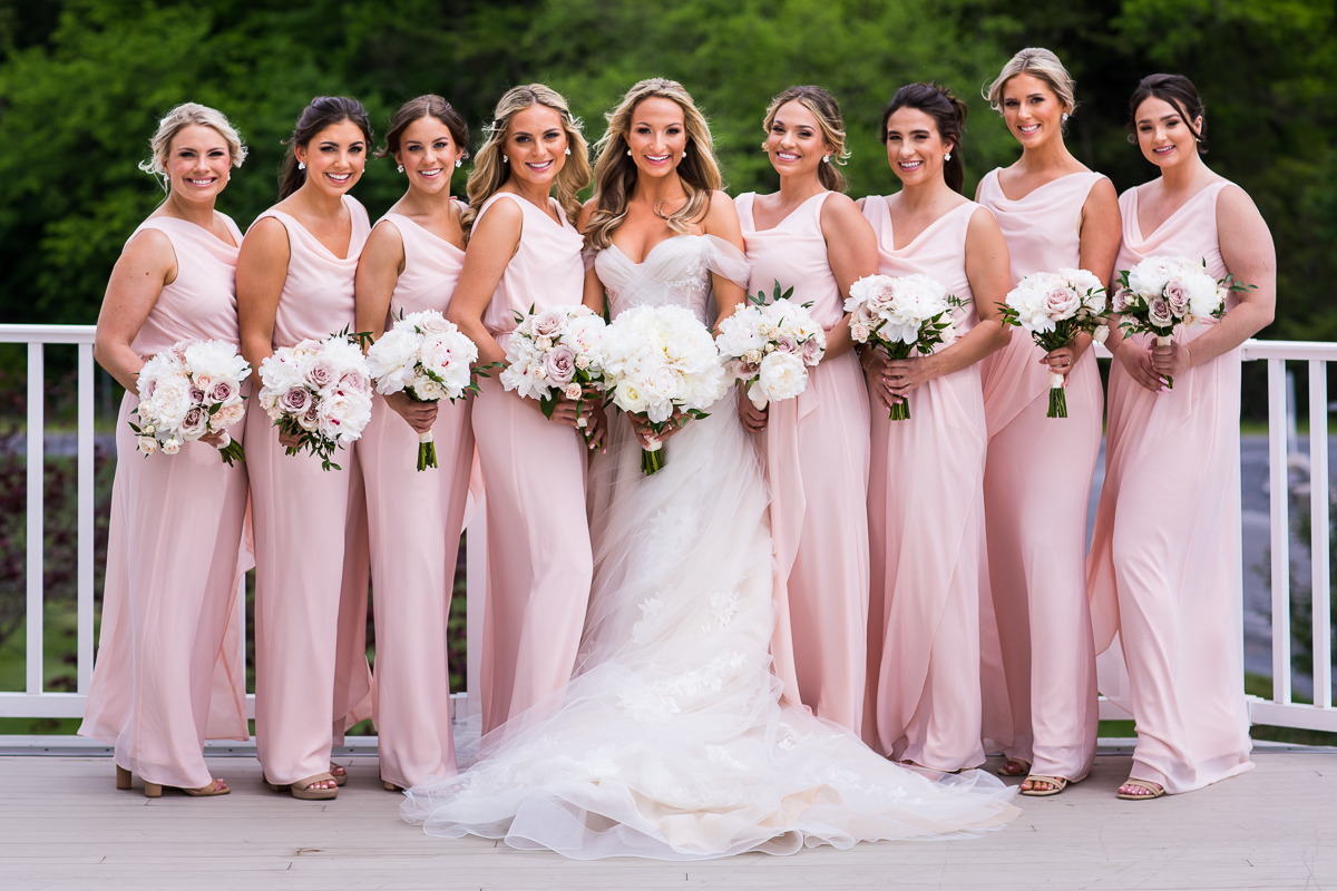 bride with bridesmaids wearing light pink dresses holding white floral bouquets outside on balcony Omni Bedford Springs best wedding photographer