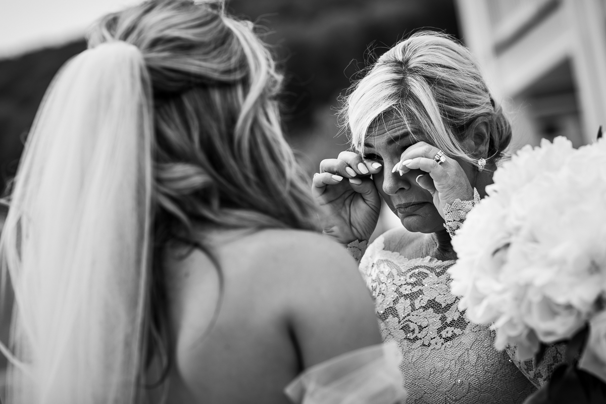 black and white emotional photo mom seeing daughter for first time on wedding day with tears