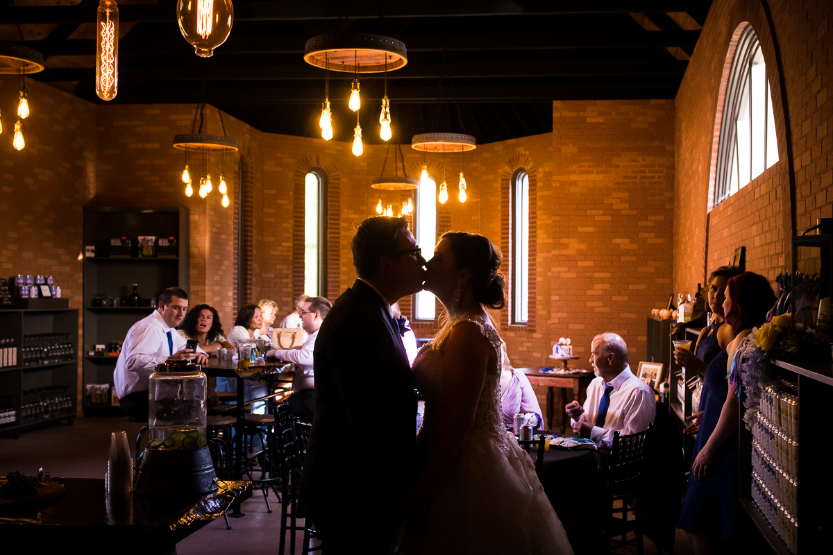 couple kisses in the mount hope estate distillery on their wedding day
